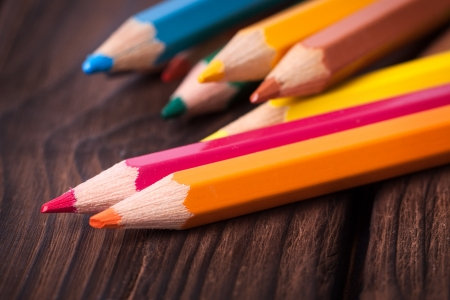 Close up of color pencils isolated on brown background photo