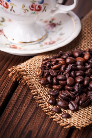 coffee beans and cup with sugar cubes on wooden background photo