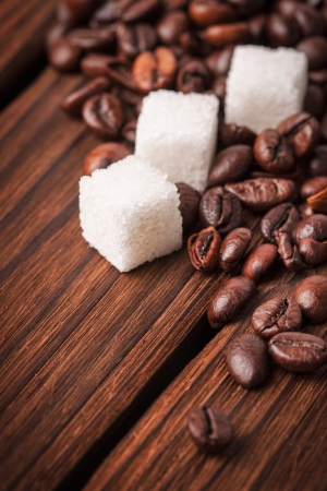 coffee beans with sugar cubes on wooden background photo