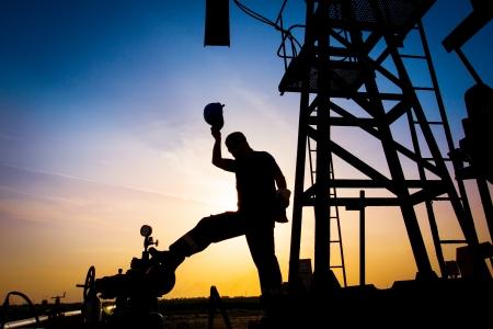 trabajador petroleros: Silueta del trabajador del petr? Foto de archivo