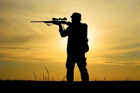 cazador: Cazador con la escopeta en la puesta del sol
