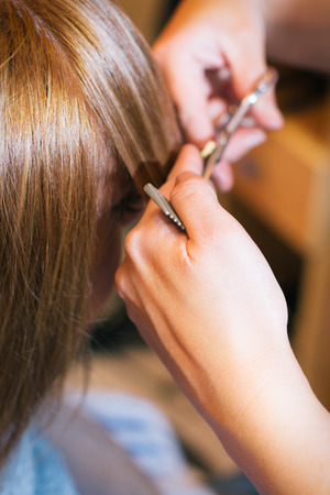 Woman at the beauty salon straightening hair photo