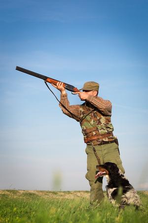 Cazador masculino en el campo de caza con perro Foto de archivo