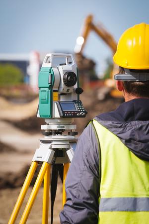 teodolito: Trabajador de la toma de ingeniero topógrafo medir con equipo herramienta teodolito en el sitio de construcción