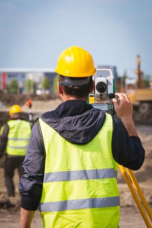 teodolito: Trabajador de la toma de ingeniero top�grafo medir con equipo herramienta teodolito en el sitio de construcci�n