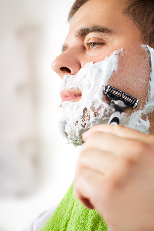 his: Man shaves his face