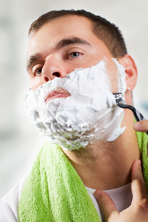 face to face: Man shaves his face