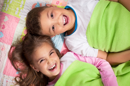 girl lying down: Brother and sister lying on the bed together