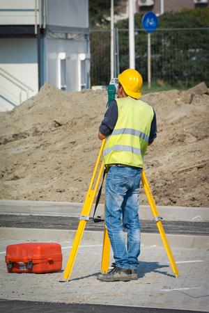 topografo: Ingenieros Surveyor trabaja con teodolito en el sitio de construcción de carreteras
