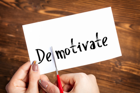 unmotivated: Woman hands cutting card with the word demotivate Stock Photo