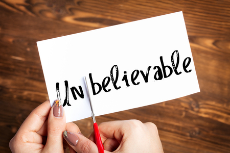 believable: Woman hands cutting card with the word unbelievable