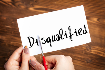 underscore: Woman hands cutting card with the word disqualified