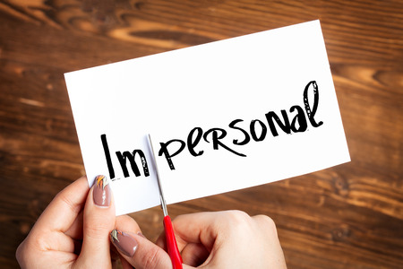impersonal: Woman hands cutting card with the word impersonal