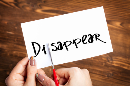 capitalized: Woman hands cutting card with the word disappear