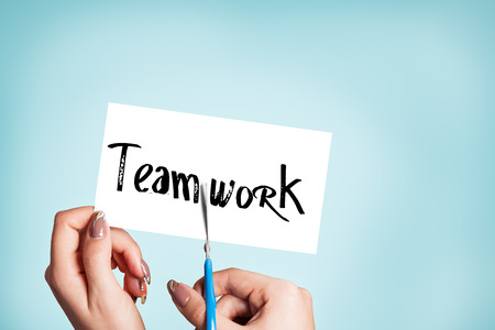 Woman hands cutting card with the word teamwork