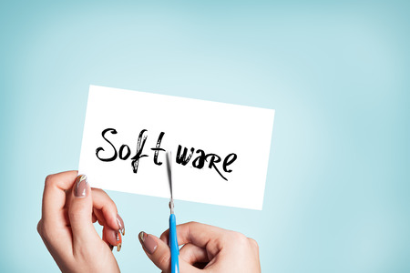 compiler: Woman hands cutting card with the word software