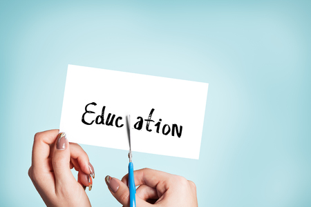master degree: Woman hands cutting card with the word education Stock Photo