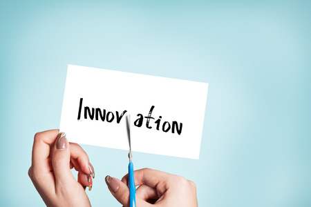 innovator: Woman hands cutting card with the word innovation