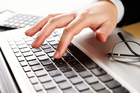 inputting: Hands of an office woman typing