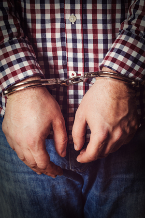 cuffed: Criminal hands locked in handcuffs on dark background
