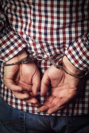 restraints: Criminal hands locked in handcuffs on dark background
