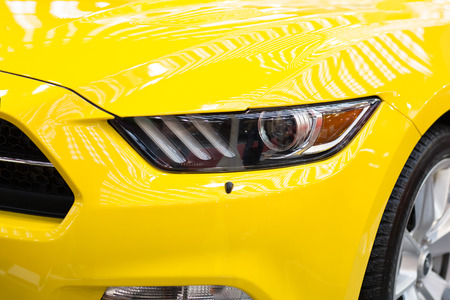 front end: Part of front end of a yellow sports  car Stock Photo