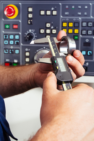 precisely: Factory man worker measuring steel detail with digital Vernier Caliper at workshop Stock Photo