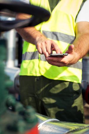 trabajador petroleros: Aceite de los trabajadores con teléfono inteligente Foto de archivo