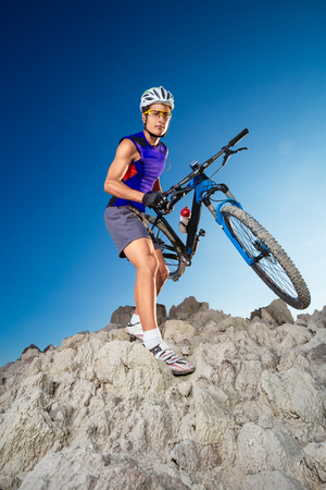 bicycle rider: Bicycle rider crossing rocky terrain Stock Photo