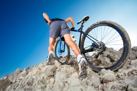 Man carrying a bike on the rock