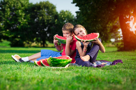 Boy and a girl eating watermelon on a sunny day Stock Photo