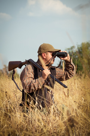 hunters: Man hunter with shotgun looking through binoculars in forest
