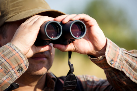 Man hunter with shotgun looking through binoculars in forest