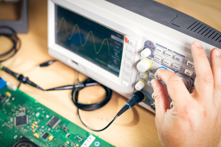 oscilloscope: Engineer tests electronic components with oscilloscope in the service center