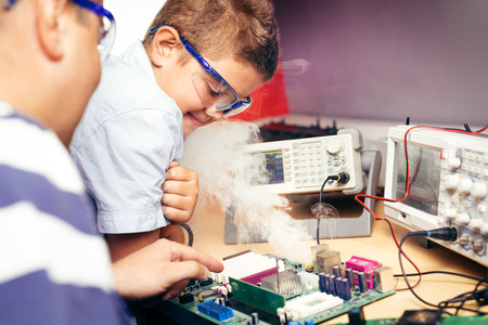 Little boy and teacher in class with electronic project Stock Photo