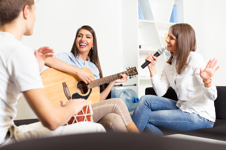 Friends enjoying playing guitar and singing together photo