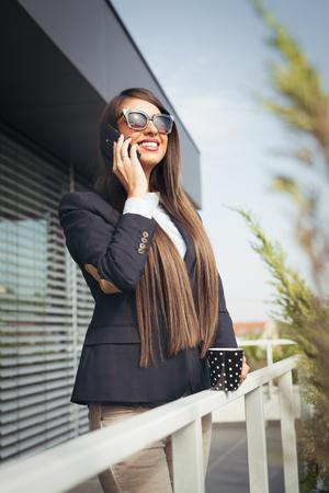 sidewalk talk: Business woman talking on smart phone Stock Photo