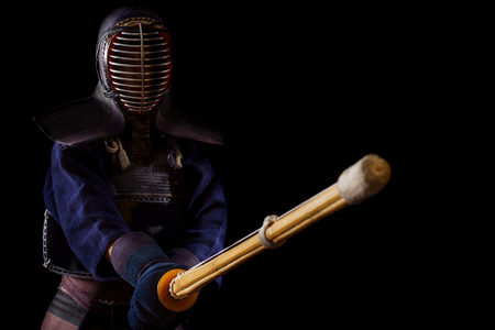 Kendo warrior in traditional dress on a black background