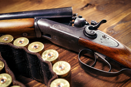 antique rifle: Shotgun with shells on wooden background