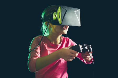 Little girl in virtual reality headset playing video-game Stock Photo