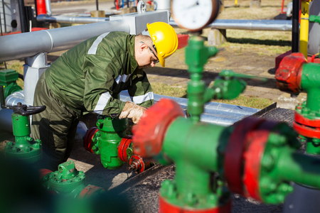Oil worker repairing wellhead valve with the wrench Stock Photo