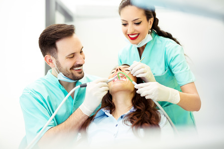 A dentist with assistant working on a patient Stock Photo