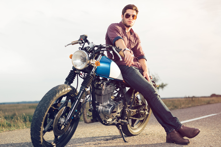 Young biker with his motorcycle