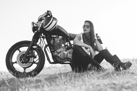 Black-and-white portrait of a beautiful biker woman sitting by her motorcycle Stock fotó