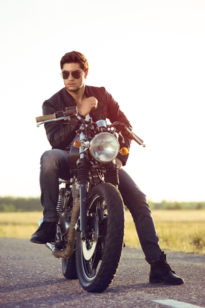 road bike: Motorcyclist with a cafe-racer motorcycle outdoors Stock Photo