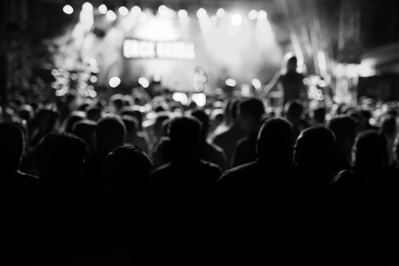 dancing club: Silhouettes of people at a concert in front of the scene in bright light. Black and White