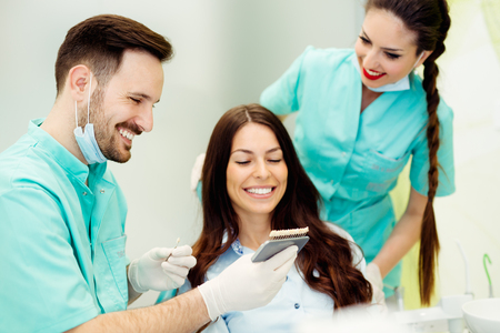 Dentist checking and selecting color of young womans teeth Zdjęcie Seryjne
