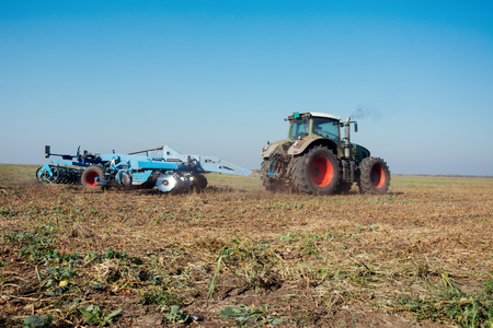 Modern tractor in a field on a sunny day. Tractor preparing land for sowing Stock Photo