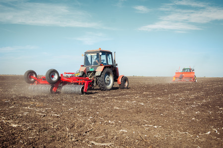 Tractor with a roller on the field at spring Stock Photo