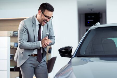 Glücklicher Geschäftsmann, der in der Nähe seines neuen Autos im Ausstellungsraum des Autohauses posiert